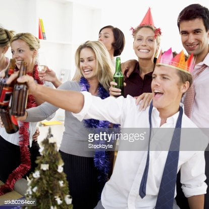 close-up of co-workers celebrating with beers at a office party : Foto de stock