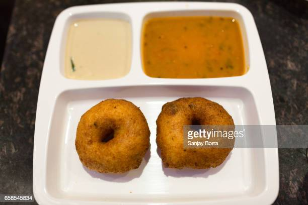 Closeup of crispy south indian vada served with chutney and sambar on a white partitioned plate