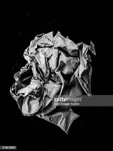 Close-up Of Crumpled Paper Against Black Background