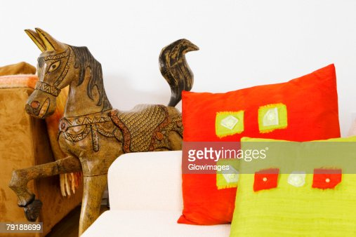 Close-up of cushions on a couch with a wooden horse : Stock Photo