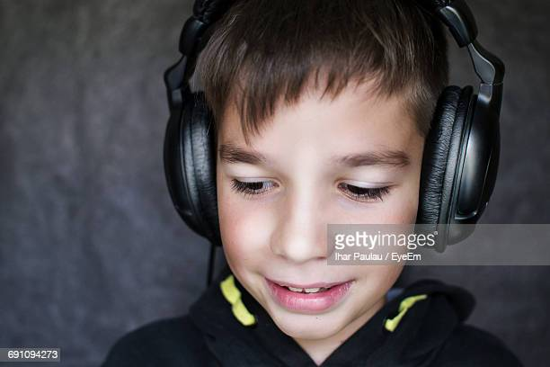 Close-Up Of Cute Boy Listening Music Against Wall