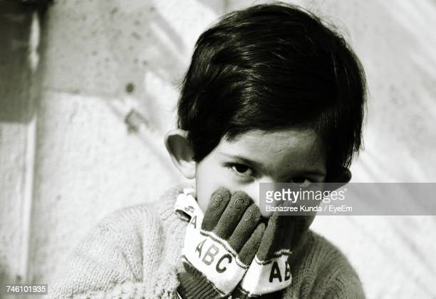 Close-Up Of Cute Boy With Hands Covering Mouth