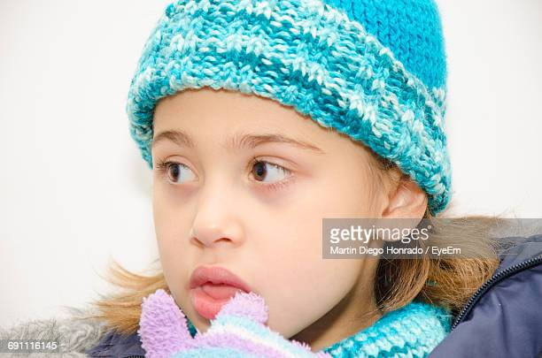 Close-Up Of Cute Girl In Warm Clothes Against White Background