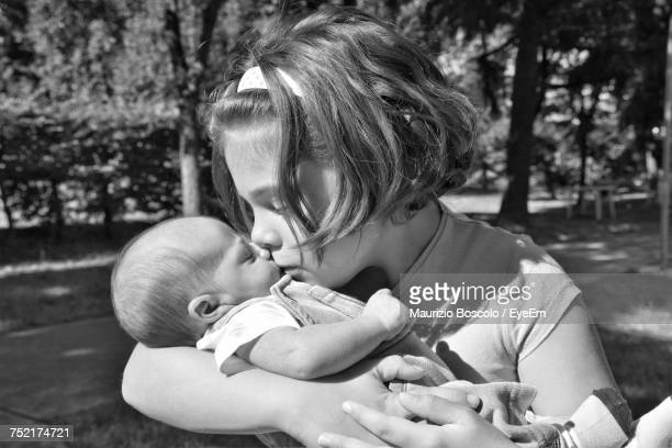 Close-Up Of Cute Girl Kissing Baby Outdoors