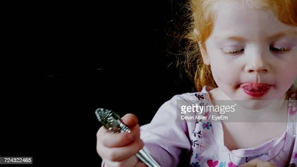 Close-Up Of Cute Girl With Spoon Against Black Background