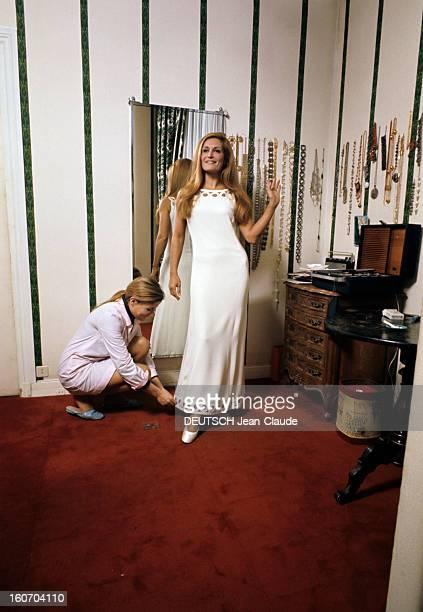 Closeup Of Dalida Dans son salon d'essayage Dalida vêtue d'une longue robe blanche bras nus pose devant le photographe sa couturieère à ses pieds...