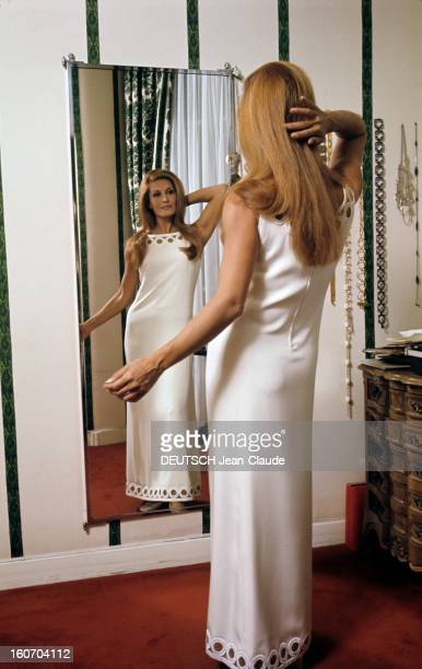 Closeup Of Dalida Dans son salon d'essayage Dalida vêtue d'une longue robe blanche bras nues pose devant un miroir sa main droite relevée en arrière...