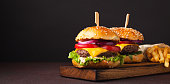 Close-up of delicious fresh home made burger with lettuce, cheese, onion and tomato on a dark background with copy space. fast food and junk food concept.