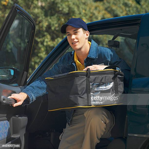 Close-up of delivery man getting out of car delivering fast food