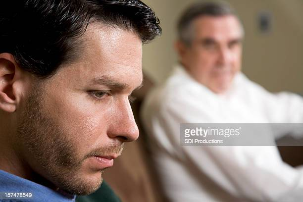 Closeup of Depressed man with father looking on