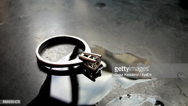 Close-Up Of Diamond Ring By Water On Table