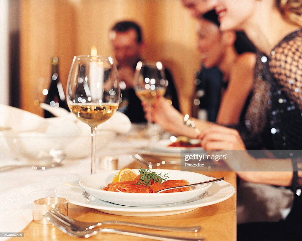 Close-up of dinner setting with salmon and wine