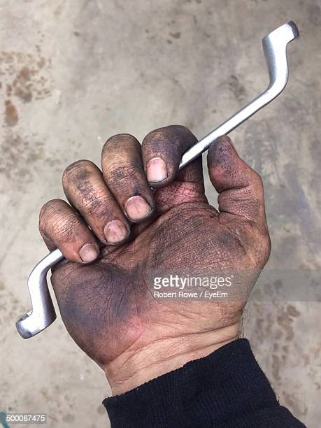 Close-up of dirty hand holding wrench