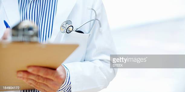 Close-up of doctor writing on a clipboard