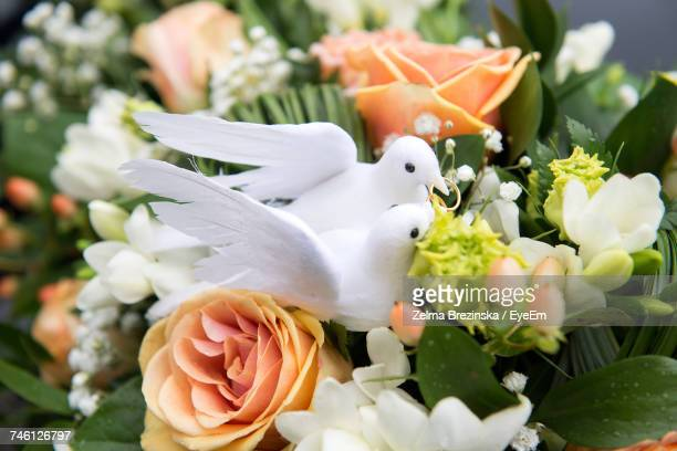 Close-Up Of Dove Figurines On Bouquet At Wedding