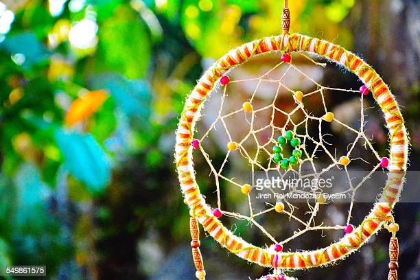 Close-Up Of Dream Catcher Against Plant In Garden