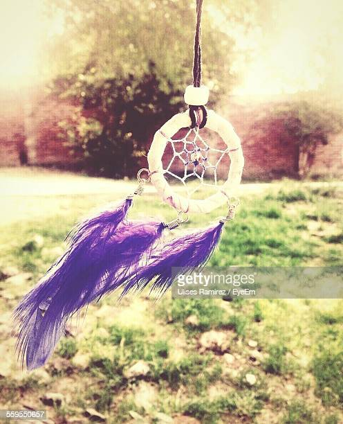 Close-Up Of Dreamcatcher Hanging By Grassy Field