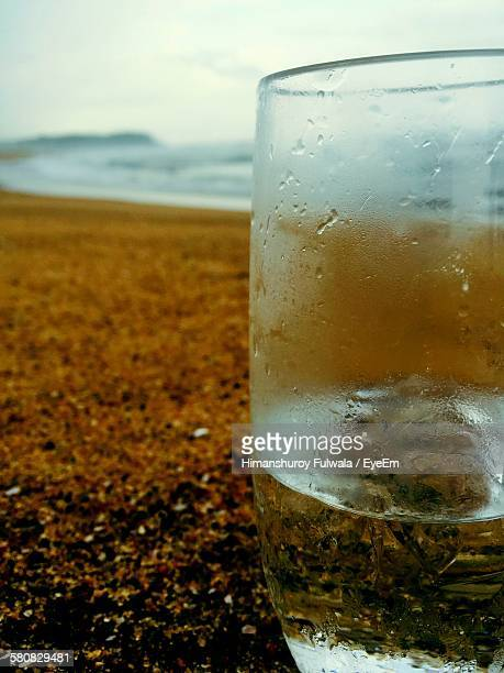 Close-Up Of Drink In Glass On Beach Against Sky