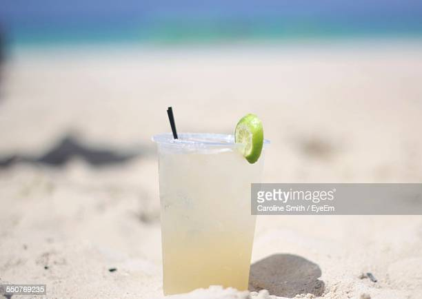 Close-Up Of Drink On Sand