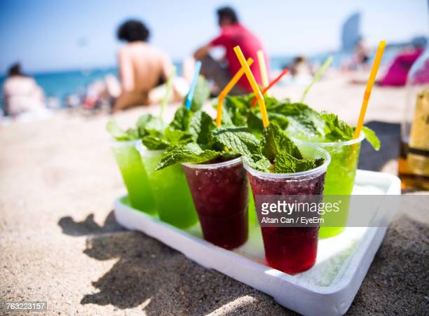 Close-Up Of Drinks In Tray On Sand At Beach