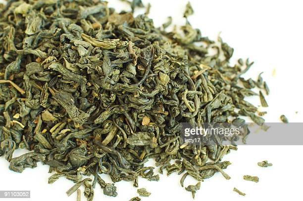 Close-up of dry green tea on white background
