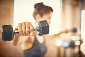 Close-up of dumbbell held by young woman. Fit female is exercising in gym. She is lifting weights.