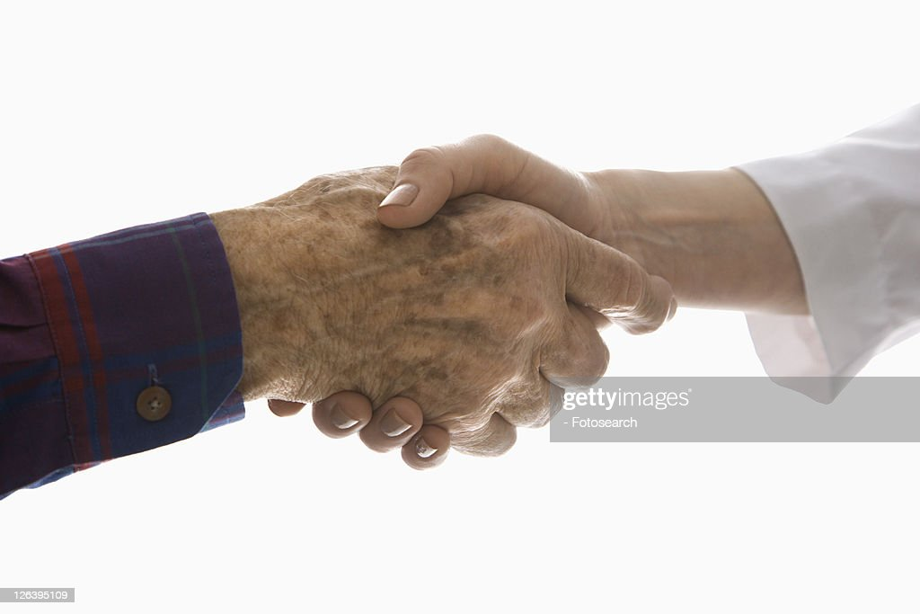Close-up of elderly Caucasian male shaking hands with mid-adult Caucasian female hand.