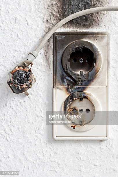 Close-up of electrical fire with the wire and wall plug