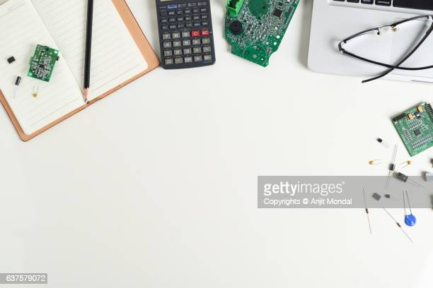 Close-up of Electronic Engineers Desk in Electronic Manufacturing Plant with Circuit Board, Electronic Components, Laptop, Calculator