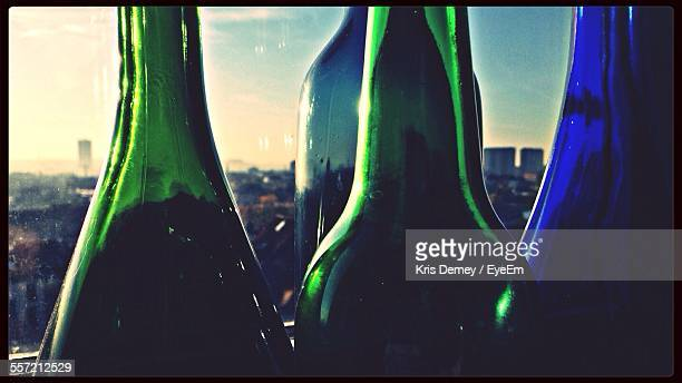 Close-Up Of Empty Bottles With City In Background
