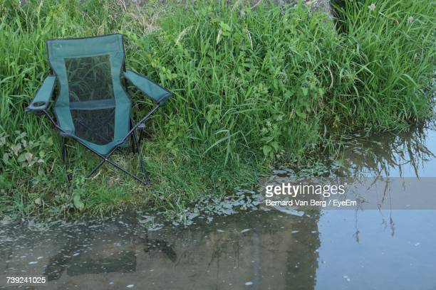 Close-Up Of Empty Camping Chair On Grass By River