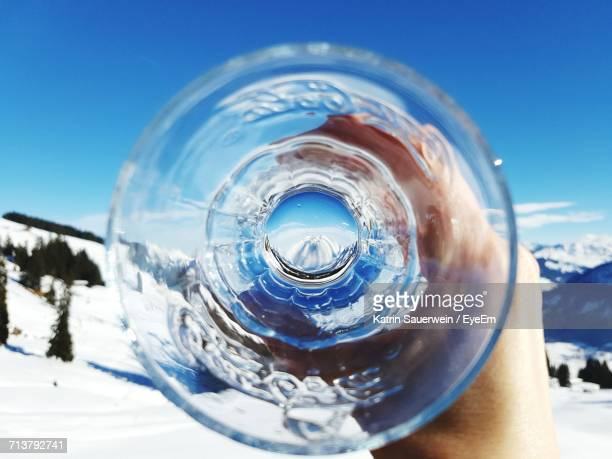 Close-Up Of Empty Drinking Glass Against Snowcapped Mountains
