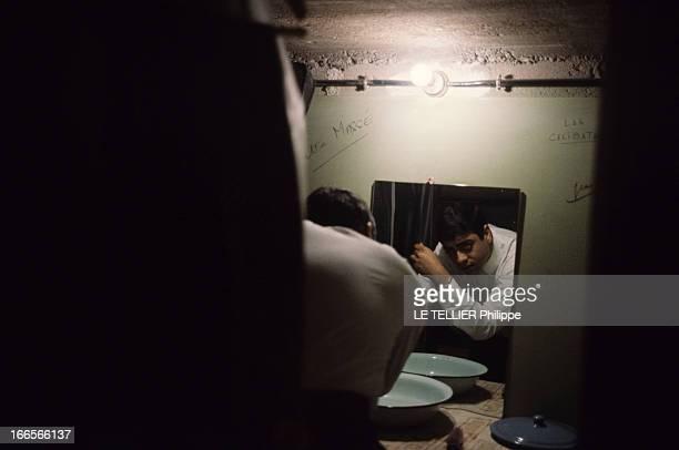 CloseUp Of Enrico Macias En 1964 Enrico MACIAS dans une pièce éclairée d'une ampoule de dos se coiffant devant un miroir et une cuvette