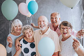 Close-up of happy, excited pensioners during a birthday party, holding colorful balloons. Active seniors concept.