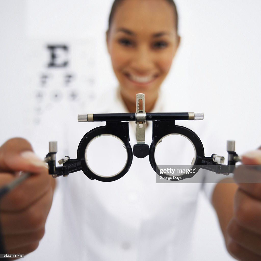 Close-up of eye testing spectacles in a young female optometrists hands (blurred) : Stock Photo