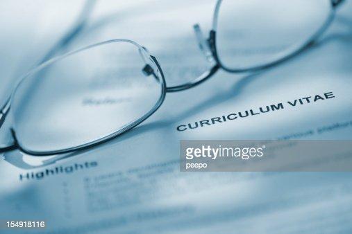 Closeup of eyeglasses on curriculum vitae.