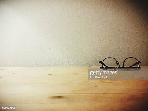 Close-Up Of Eyeglasses On Table Against Wall