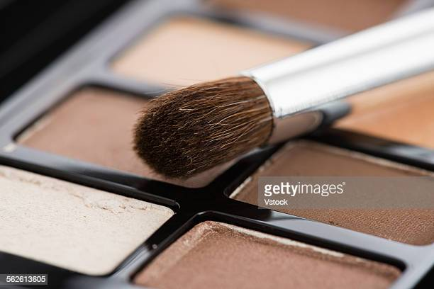 Close-up of eyeshadow palette with make-up brush