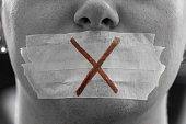 """A male face with a taped mouth and a red cross on it symbolizing censorship.Censorship is all around.Freedom of speech is the political right to communicate one's opinions and ideas via speech. The t"