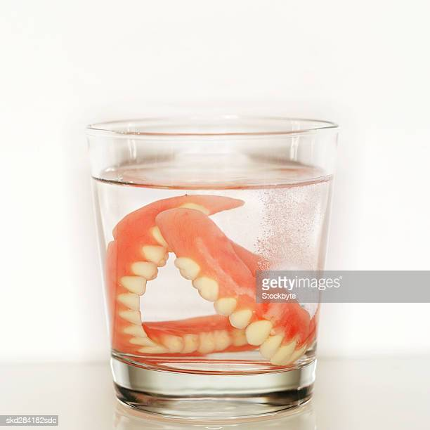 Close-up of false teeth in glass of water