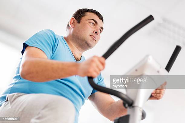 Close-up of fat man training on exercising bike.