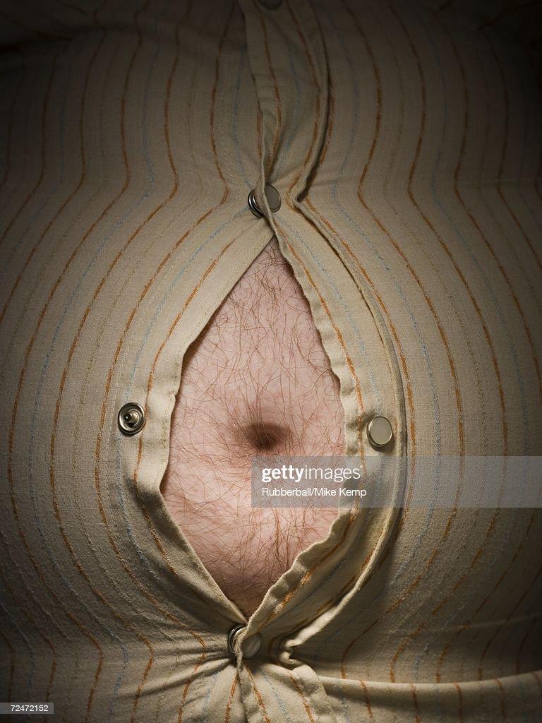 Close-up of fat stomach bursting through shirt