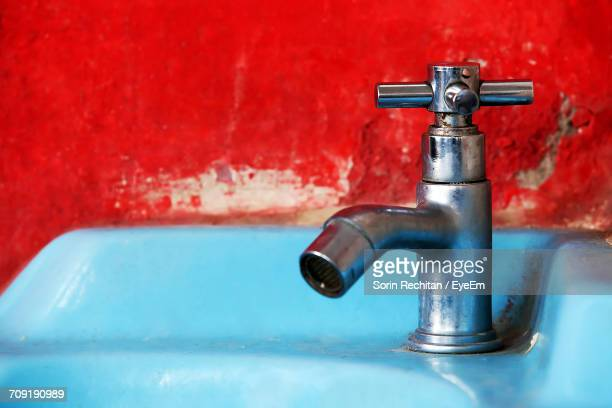 Close-Up Of Faucet On Sink By Red Wall