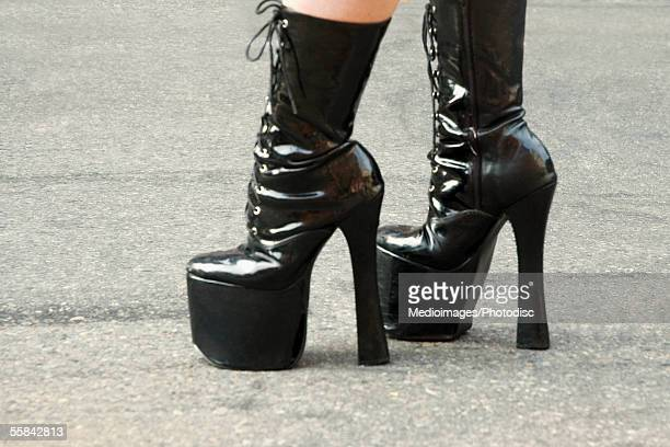 Close-up of feet of someone wearing black, stiletto platform boots