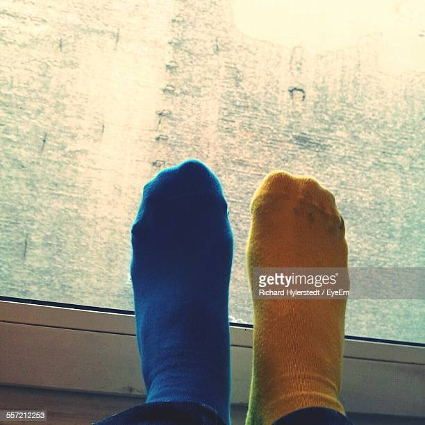 Close-Up Of Feet Wearing Blue And Yellow Socks