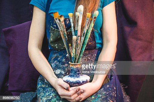 Closeup of female artist hands with paintbrushes : Foto de stock
