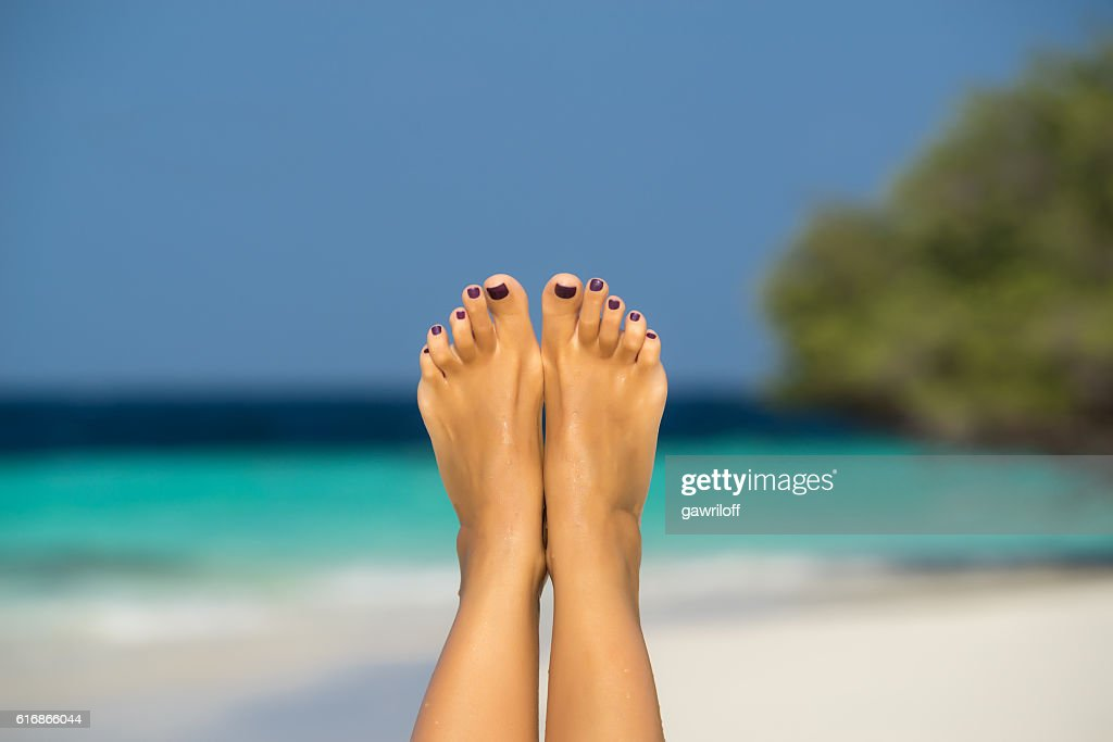 Close-up of female foot in the blue water : Stock Photo