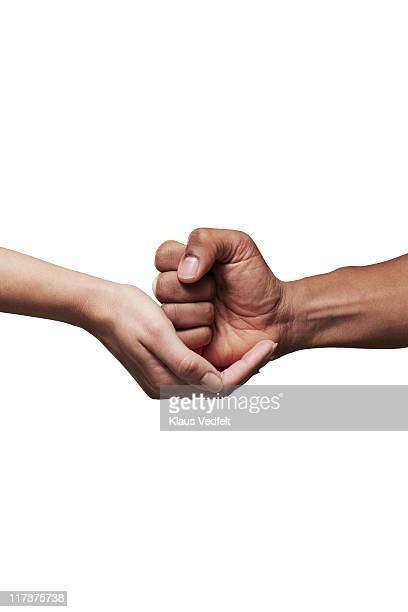 Closeup of female hand grabbing male fist