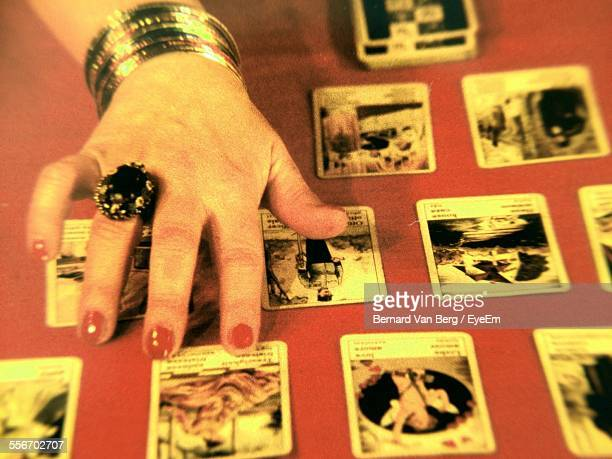 Close-Up Of Female Hand Placing Tarot Cards On Table