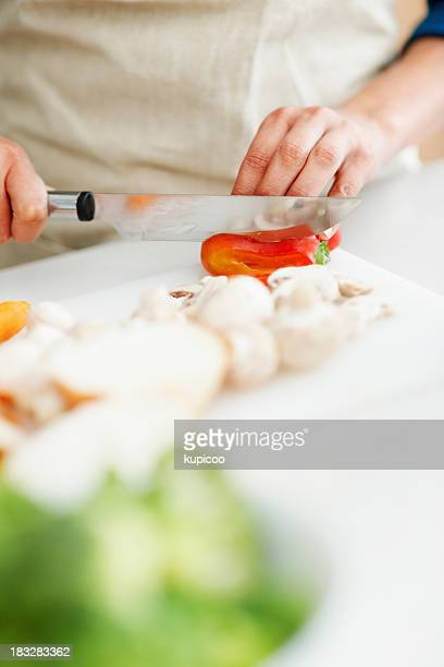 Closeup of female hands chopping vegetables in the kitchen
